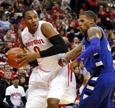 Ohio State's Jared Sullinger (0) goes to the basket as North Carolina-Asheville's P.J. Primm, right, defends during the first half of an NCAA college basketball game Tuesday, Dec. 21, 2010, in Columbus, Ohio. (AP Photo/Terry Gilliam) NYTCREDIT: Terry Gilliam/Associated Press Published 12-26-2010: Jared Sullinger has earned the praise of opposing coaches for his skills and unselfish play. At left, the Sullinger family. Pictured from left to right are Jared, Julian, Barbara, Satch and J. J. (Left, courtesy of the Sullinger family; Terry Gilliam/Associated Press)
